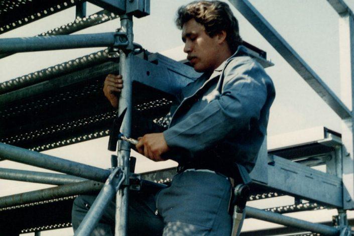 Mann beim Gerüstaufbau
